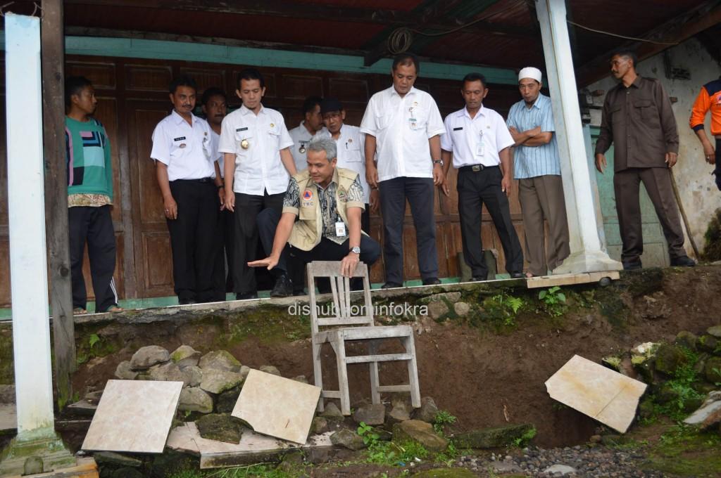 Gubernur Jawa Tengah Ganjar Pranowo, saat membandingkan tinggi kursi dengan kedalaman amblasan tanah, Rabu (28/01) di depan rumah Wagiman.